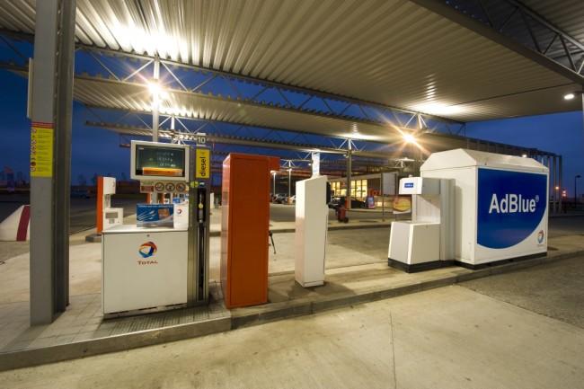 Vue d'un îlot carburant réservé aux camions, placé sous le auvent de la station autoroutière atypique de Hellebeq, en Belgique. A côté du volucompteur, une borne pour le gonflage des pneumatiques et plus à gauche un réservoir Ad Blue. A l'arrière plan, la boutique Bonjour. Prise de vue réalisée de nuit, avec les différents éclairages de la station actifs.