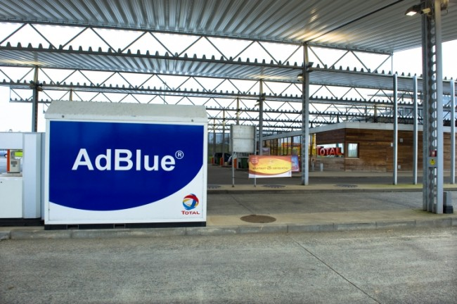 Vue d'un îlot carburant réservé aux camions, placé sous le auvent de la station autoroutière atypique de Hellebeq, en Belgique. Un réservoir Ad Blue est placé à côté du volucompteur. A l'arrière plan à droite, la boutique Bonjour.